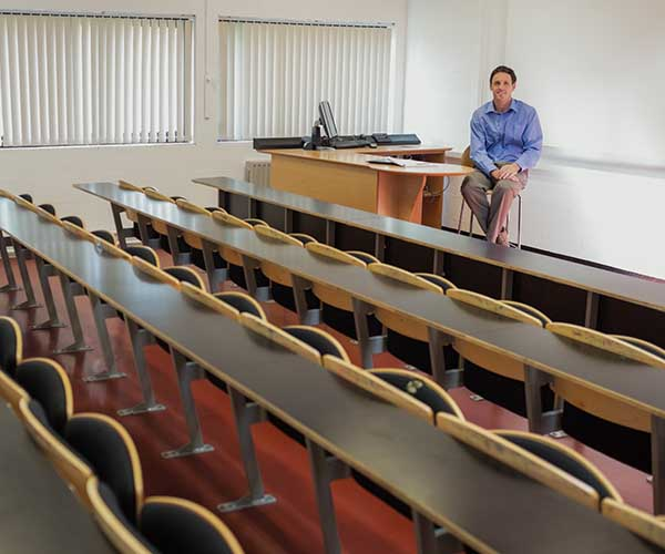 Portrait of an elegant male teacher sitting in the lecture hall